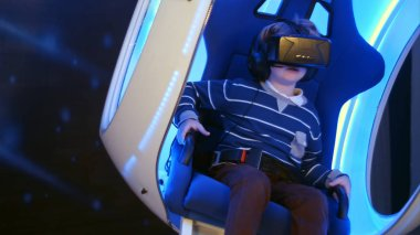 Little boy experiencing virtual reality sitting in interactive moving chair