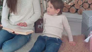 Capricious boy listening to his mom reading a book near Christmas tree