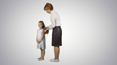 Happy mother doing hair style for a daughter on white background