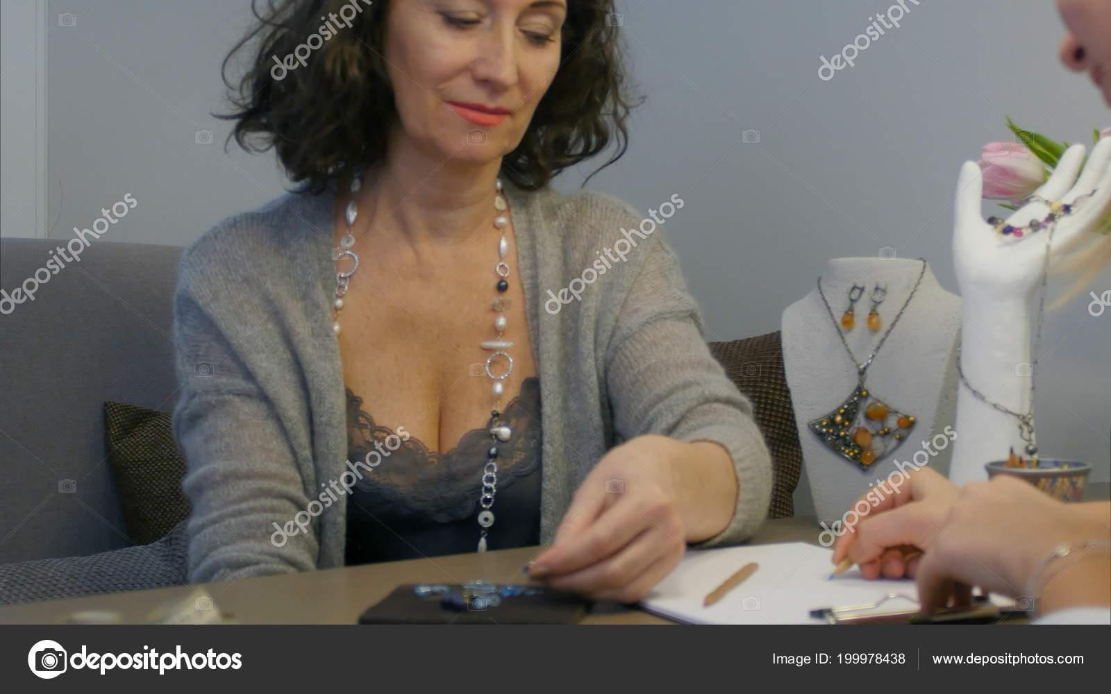 Elegante Donna In Studio Selezionando Disegni Di Gioielli E Designer