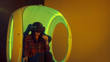 Young woman experiencing virtual reality sitting in interactive moving chair