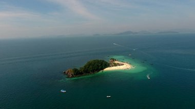 Aerial view, camera flies around thewild island in the sea at sunny summer day