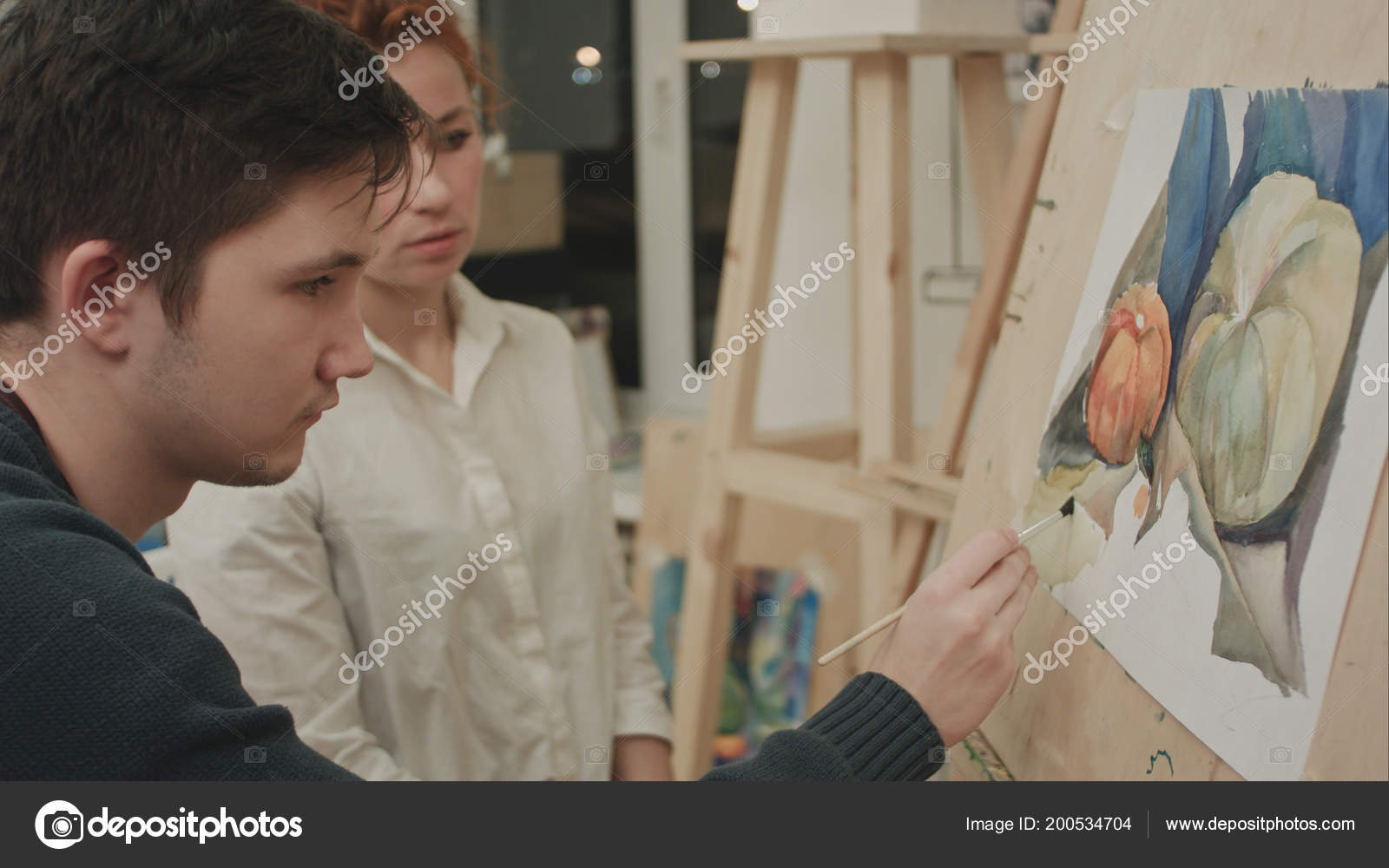 Female artist teaching young male student to paint with