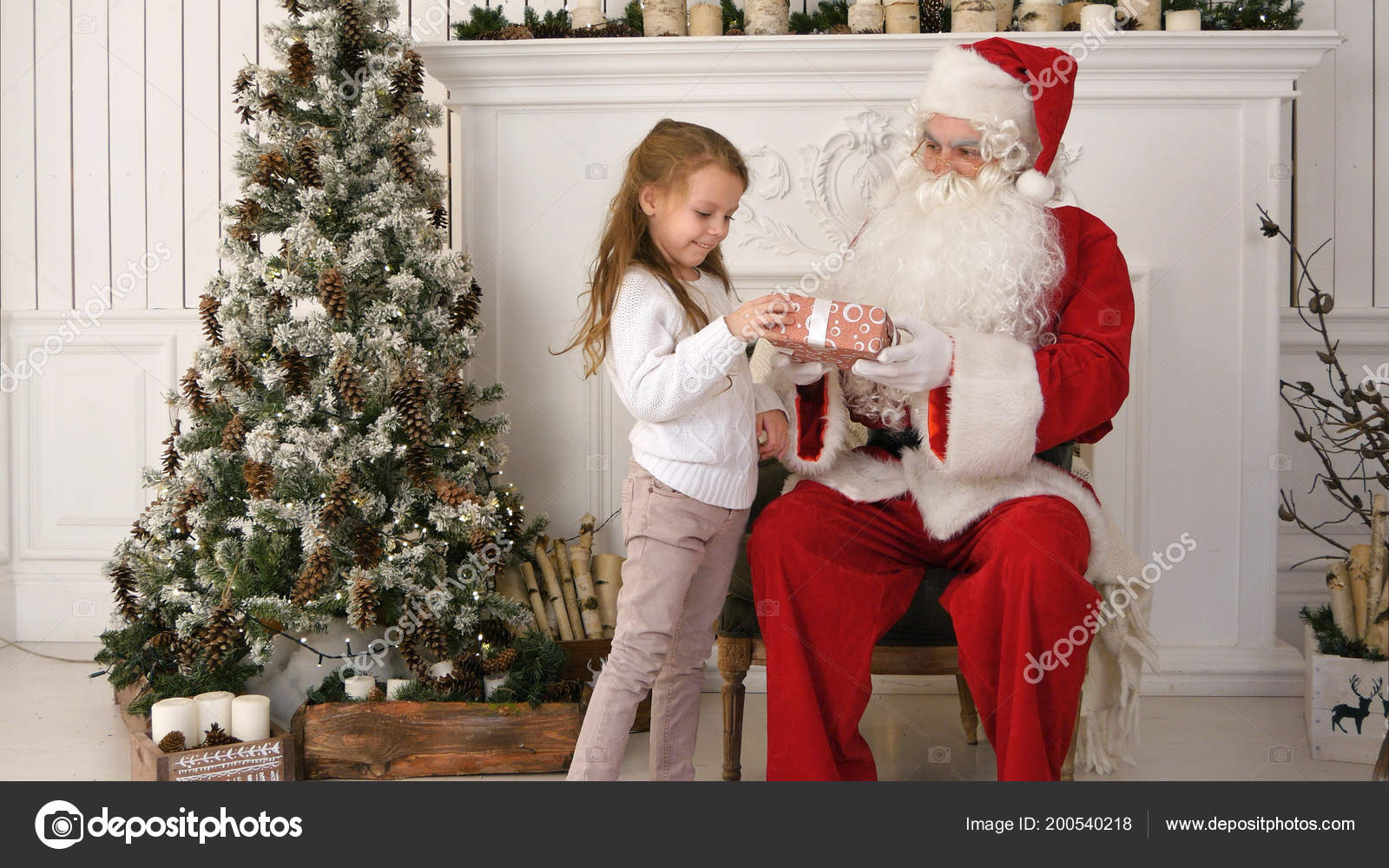 Pretty little girl presenting Santa Claus with Christmas gift ...