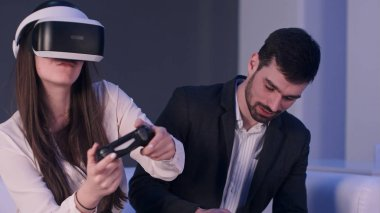 Smiling young man with phone trying to stop girl in VR headset from playing so much