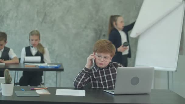 Child boss on the phone working on laptop