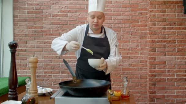Hezký šéfkuchař připravuje pánev s těstem a mluví do kamery
