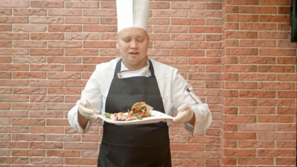 Barátságos chef egységes jelen a lemez, a tenger gyümölcsei saláta beszél a kamera