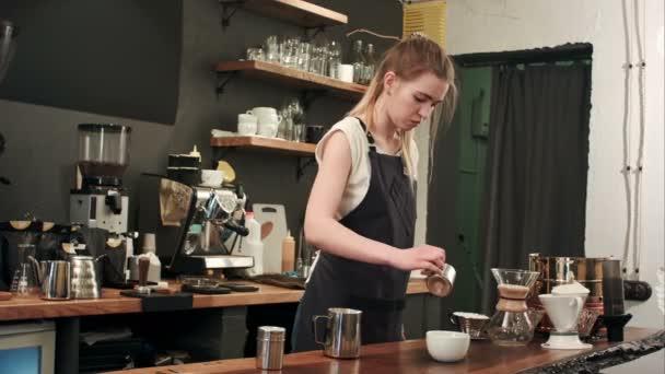 Barista szakadó kávé és a tej egy csésze a kávézóban