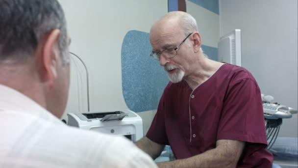 Reifer Arzt am Schreibtisch, macht Notizen, hört einem älteren Patienten zu
