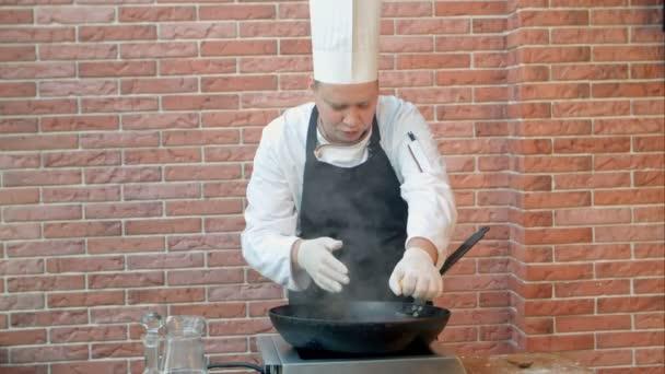 Koch im Restaurant Kochen gebratene Knödel mit Meeresfrüchten in Pfanne, Zitronensaft auspressen