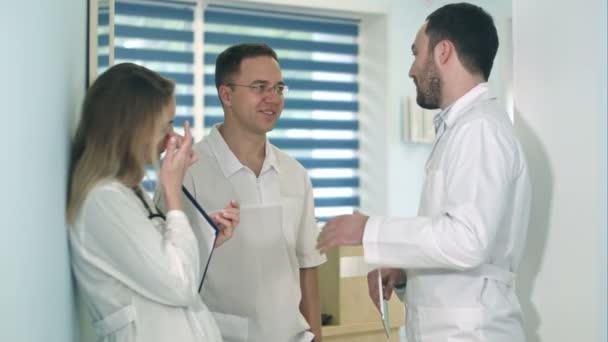 Arzt mit Tablet im Gespräch mit zwei anderen Ärzten im Krankenhausflur