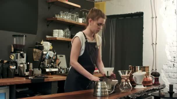 Barista macht handgebrühten Kaffee, fügt gemahlenen Kaffee hinzu und gießt heißes Wasser ein
