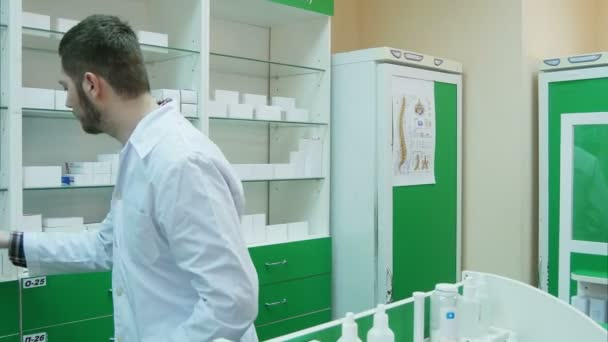 Young pharmacist giving box of tablets to customer and taking payment in dollars