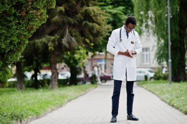 Stylish african american doctor with stethoscope and lab coat, at glasses posed outdoor.