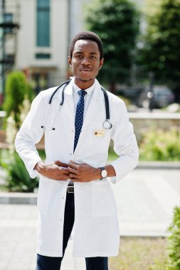 Stylish african american doctor with stethoscope and lab coat posed at backyard of hospital.