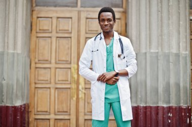 Stylish african american doctor with stethoscope and lab coat posed against door of hospital.