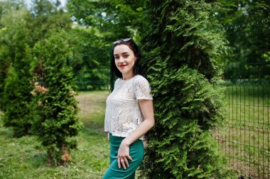 Brunette girl in green skirt and white blouse posed at park.