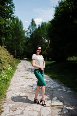Brunette girl in green skirt and white blouse with sunglasses posed at park.