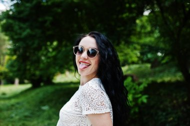 Brunette girl in white blouse with sunglasses posed at park.