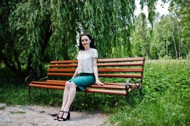 Brunette girl in green skirt and white blouse posed at park, sitting on bench.