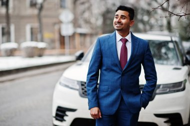 Elegant indian fashionable man model on suit posed at winter day against white business suv car.