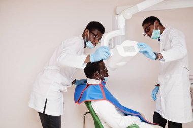 African american male doctors in professional uniform taking x-ray of patient.