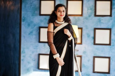 Young indian woman wear at elegant black saree posed on restaura