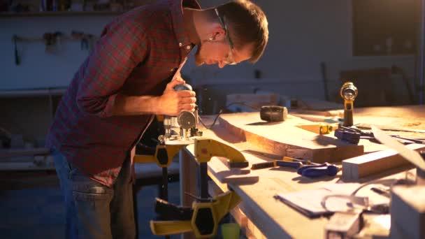 Tesař pracuje ve své dílně jako automatický elektrický fréza na dřevo.