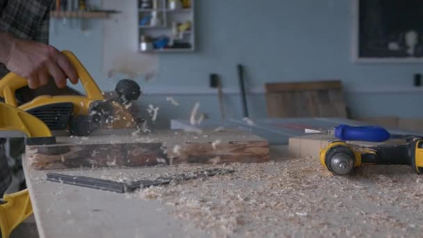 A carpenter works with an electric planer in his carpentry workshop. Slow motion footage with natural light frame.