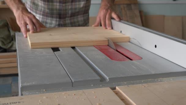 Tesař zpracovává dřevěné slepé na kruhové pilě v truhlářské dílně.