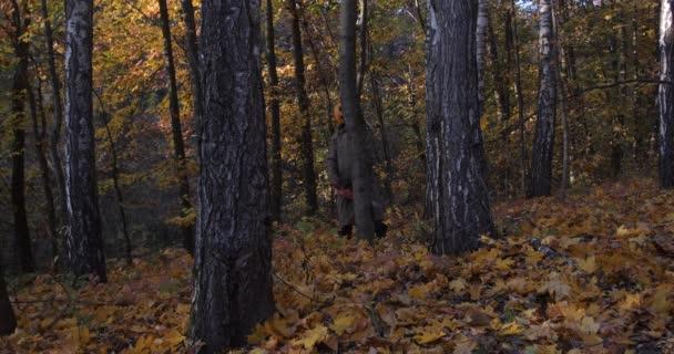 Halloween koncept. Šílený dýňový muž s motorovou pilou v podzimním lese