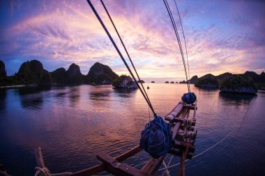 Sunset illuminates limestone islands and a gorgeous lagoon in Wayag, Raja Ampat, Indonesia. This tropical region is known as the heart of the Coral Triangle due to its incredible marine biodiversity.