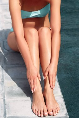 Beautiful  Legs Outdoors By Pool Under Sunshine On Summer Day. Skincare.  Protection Sun. Epilation Laser or Shaving Concept.Sunscreen on Feet