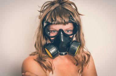 Young naked woman with gas mask isolated on gray background - retro style