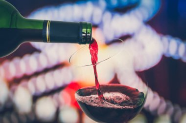 Red wine pouring into a wine glass - celebration concept - retro style
