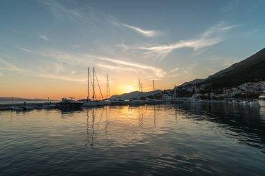 Sunset in Baska Voda town with Adriatic Sea and boats, Croatia