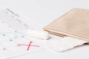 Planning pointing at date in calendar with menstrual  tampons concept
