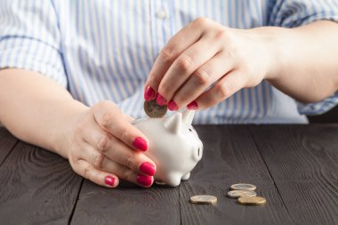Close-Up Woman Hand is Putting a Money Coin into Piggy Bank on table