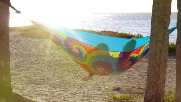 Boldog lány a nyaralás pihentető függőágy. Barátnők figyelte a naplemente szivárvány színek függőágy között pálmafák, nyaralás a tengerparton. Lencse fényfolt hatása. Retro és a szüret hang