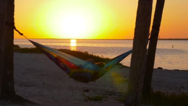 Zwei Mädchen wackeln in Hängematte zwischen Palmen und Foto Sonnenuntergang. Freundinnen Sonnenuntergang in Regenbogen Farben Hängematte zwischen Palmen im Urlaub am Strand. Warmes Licht abgeschwächt