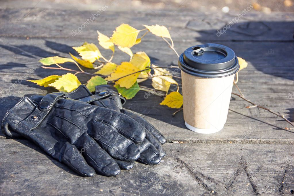 Glass of coffee, gloves and autumn leaves on a wooden background