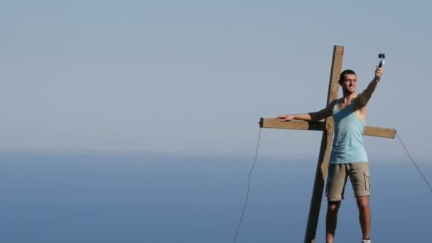 Fiatal férfi örömmel veszi magát a cselekvési kamera, tetőn a kereszt közelében. Elérése a cél, motiváció