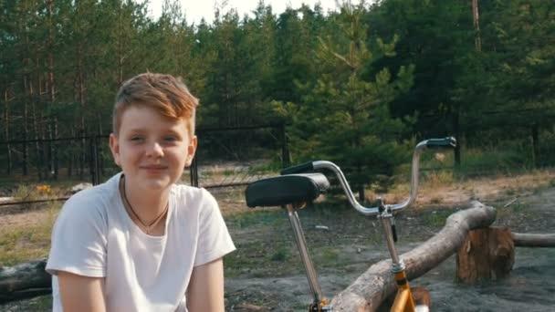 Roztomilá blondýnka s modrýma očima dospívající chlapec sedí a úsměv v parku vedle kola a rozhovory v létě. Emocionální portrét chlapce