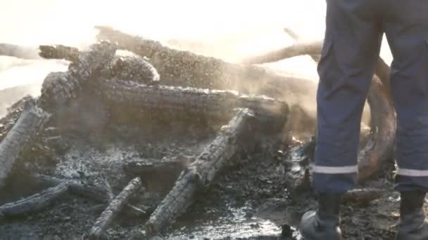 Hasič hasí oheň z hasičské hadice. Vypálit na uhlí, černé stromy kouře na pozadí nohou lidí