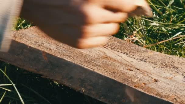 Mann hämmert langen Nagel in alte Bretter