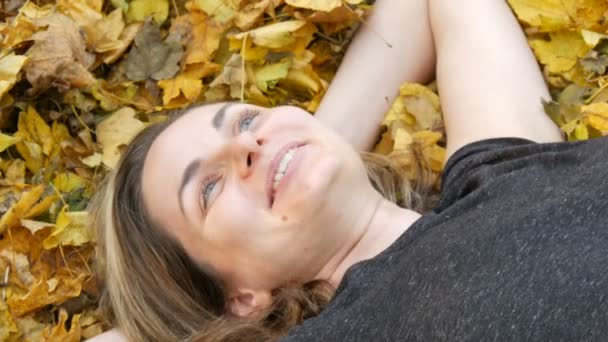 Portrait of the face of beautiful young girl without makeup who lies in the autumn yellow foliage and enjoys life. Dry autumn leaves fall on the face of a laughing woman