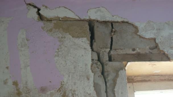 Velké otvory a praskliny v betonové zdi
