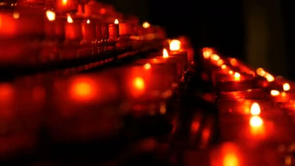 Burning memorial candles in Catholic church  Row of christian prayer red  round votive candles burn in the dark  Prayer lighting Sacrificial Candles  close up  Celebrating christmas in Cathedral