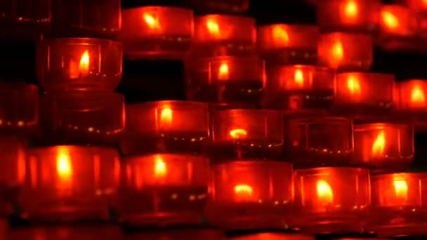 Row of christian prayer red round votive candles burn in the dark  Prayer  lighting Sacrificial Candles close up  Burning memorial candles in Catholic  church  Celebrating christmas in Cathedral